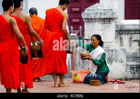 Laos. Luang Prabang, World heritage of UNESCO since 1995. Lao buddhist monks collecting alms on early morning - Stock Photo