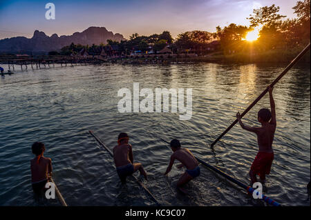 Laos. Vang Vieng. Province of Vang Vieng. Boys playing in the Nam Song river at sunset - Stock Photo