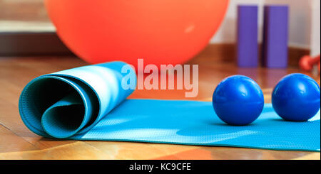 Fitness equipment. Pilates mat and exercise weights on wooden floor - Stock Photo