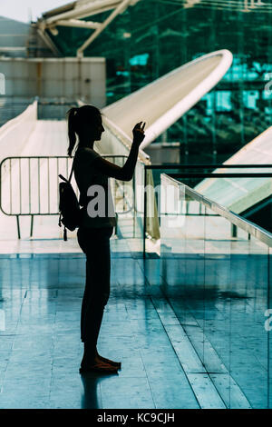 Silhouette Against Light Of Young Woman Taking Photos In Modern Building - Stock Photo