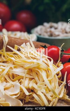 Close-up of unprepared italian pasta with fresh tomatoes - Stock Photo