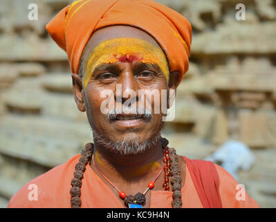 Middle-aged Shaivite sadhu with orange turban, red tilaka mark and yellow sandalwood paste on his forehead, rudraksha - Stock Photo