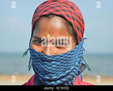 Young Tamil low-caste female street sweeper, covering her nose and mouth with a blue-and-black checkered dust bandana - Stock Photo