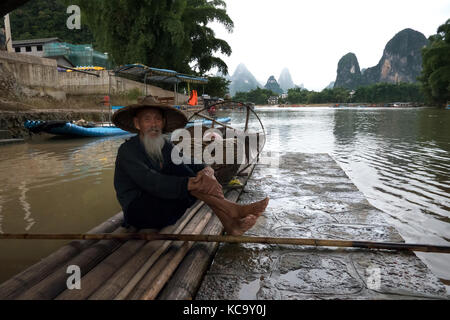 Old Chinese fisherman on bamboo draft posing with cormorants on Li River near Xingping, between Yangshuo and Guilin, - Stock Photo
