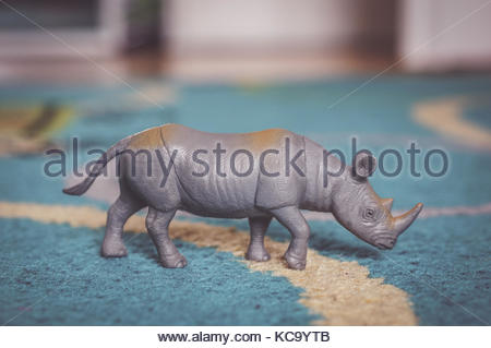 Plastic toy rhinoceros standing on a blue carpet in soft focus - Stock Photo