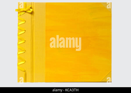 Yellow hand crafted book with STAB binding bound with bookcloth and hand decorated paper, sewn with ribbon isolated - Stock Photo