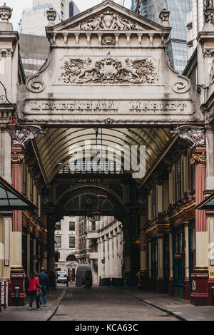 Couple walking into Leadenhall Market, popular market in London that was built in the 19th century. - Stock Photo