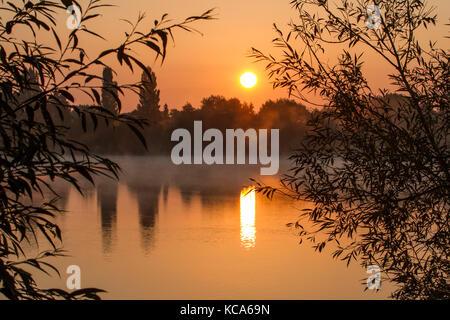 Sunrise over a calm lake on a misty autumnal morning, UK - Stock Photo