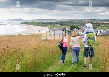 A fmaily of four are walking along the sand dunes. The little boy is getting carried on his fathers shoulders. - Stock Photo