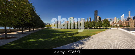 Panoramic Summer view of Franklin D. Rosevelt Four Freedoms Park lawn with the skyscrapers of Manhattan Midtown - Stock Photo
