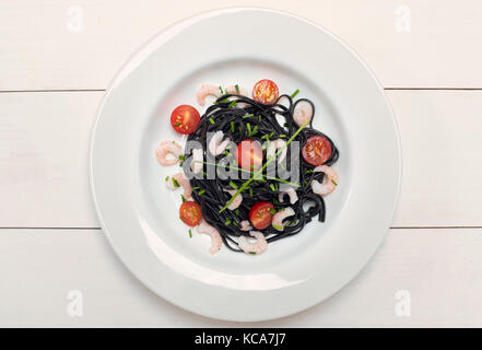 Squid ink black pasta with prawns, chives and tomatoes on a white background