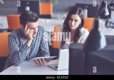 Young Casual business couple using computer in the office. Coworking, Creative manager showing new startup idea - Stock Photo