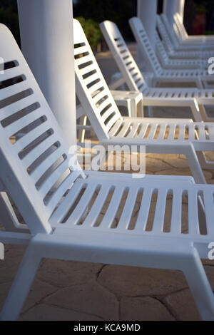 White plastic sun beds and loungers in a row next to a pool going grdyually out of focus and tapering away in a - Stock Photo