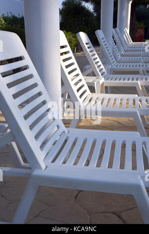 a row or line of sun beds or loungers in white in the shade next to a pool at a hotel in the sun tapering away and - Stock Photo