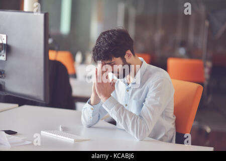 young business man working on desktop computer at his desk in modern bright startup office interior - Stock Photo