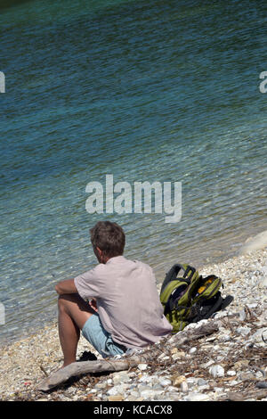 a man sitting on the beach on his own. Thinking time alone. - Stock Photo
