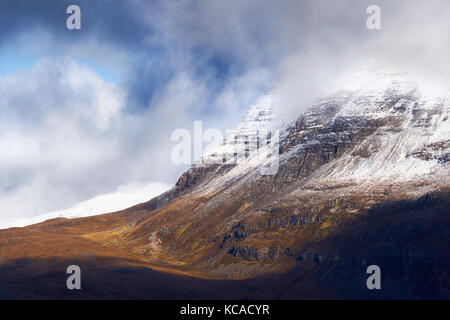 A snow and cloud covered summit of Slioch above Loch Maree in the Scottish Highlands, Scotland, UK. - Stock Photo