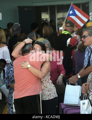 Fort Lauderdale, Florida, USA. 03rd Oct, 2017. Victims of Hurricane Maria embrace with waiting family members at - Stock Photo