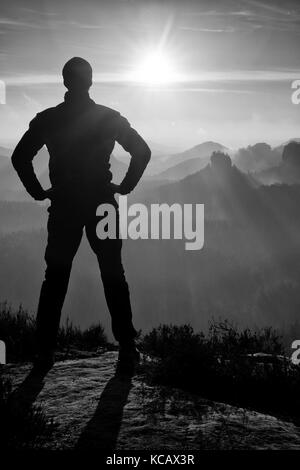 Self confident hiker on the peak of sandstone rock in rock empires park and watching over the misty and foggy morning. - Stock Photo