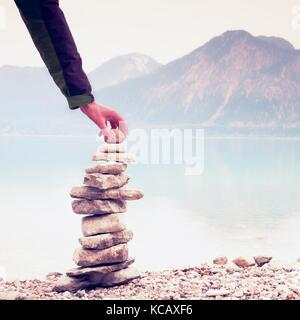 Man built pyramid from pebbles. Balanced stone pyramide on shore of blue water of mountain lake. Blue mountains - Stock Photo
