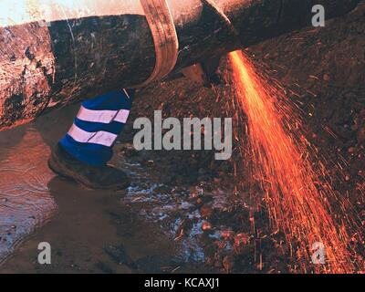 Worker staff is cutting big metal tube with hand grinder. Burning parks are flying down to wet clay. Staff use safety - Stock Photo