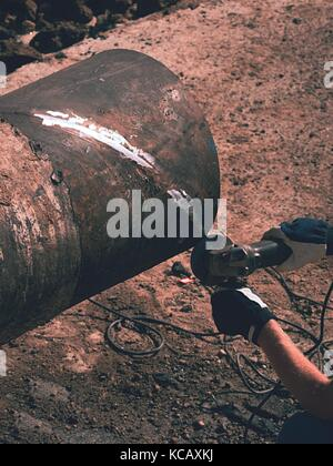 Worker underground with hand grinder is cutting big metal tube. Sparks are flying down to wet clay. Working staff - Stock Photo