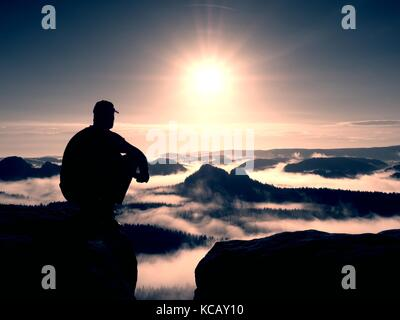 Moment of loneliness. Man with cap sit on the peak of rock and watching into colorful mist and fog in forest valley. - Stock Photo
