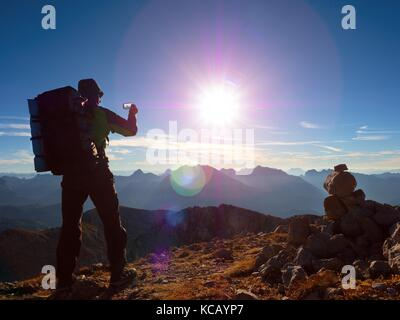 Lens flare light, strong defect. Hiker takes selfie photo. Man with big backpack and poles walk on Alpine mountain. - Stock Photo