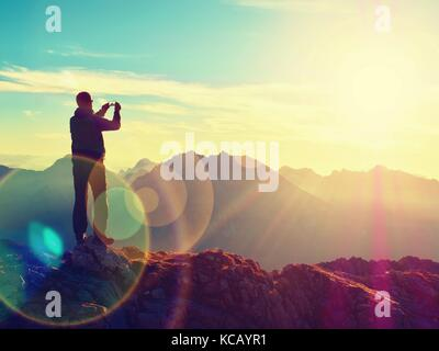 Lens flare light, strong effect. Bow light circles.  Hiker takes selfie photo. Tourist at mountain peak. Daybreak - Stock Photo