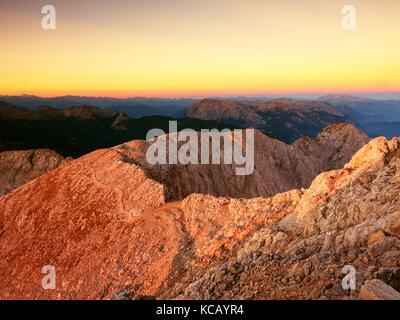 Morning view over Apine  cliff and valley.Daybreak Sun at horizon. Mountains increased from foggy background - Stock Photo