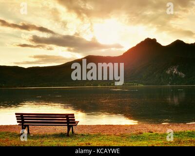 Empty bench at spring mountain lake. The coast with mountains at horizon and in water mirror. Vintage toned photo. - Stock Photo