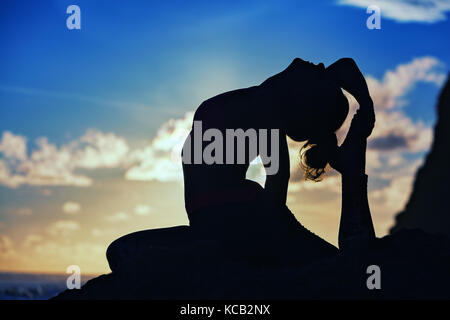 Woman black silhouette on sunset sky background. Young active girl sit in yoga pose on beach rock, stretching to - Stock Photo