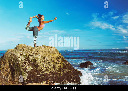 Meditation on sunset sky background. Young active woman stand in yoga pose on beach rock to keep fit and health. - Stock Photo