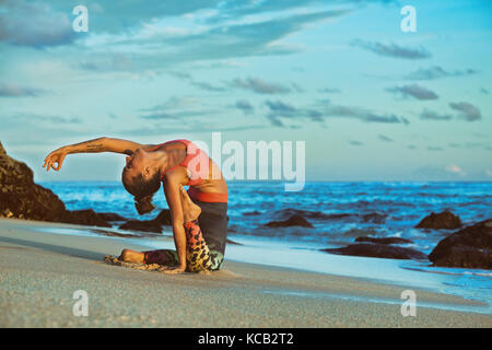 Meditation on sunset sky background. Young active woman sit in yoga pose on sand beach, stretching to keep fit and - Stock Photo