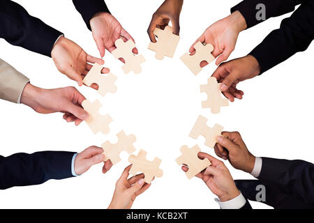 High Angle View Of A Businesspeople Hand Holding Jigsaw Puzzle On White Background - Stock Photo