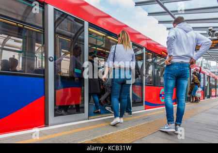 Passengers / commuters boarding a train during daytime, at Royal Victoria station, on Docklands Light Railway (DLR) - Stock Photo