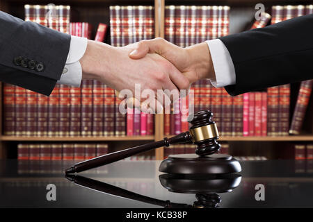 Gavel On Table With Judge And Client Shaking Hands In Background At Courtroom