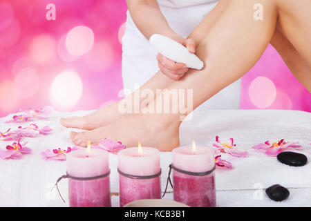 Close-up Of A Beautician Using Laser Machine On Customer's Leg At Beauty Spa - Stock Photo