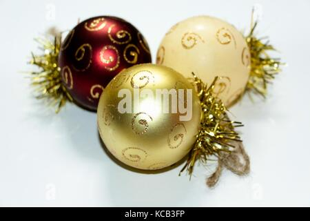 Three multi-colored Christmas decorations in the shape of a balloon, painted with gold patterns. A composition of - Stock Photo