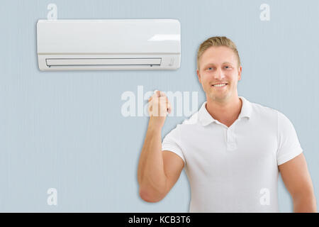 Portrait Of A Young Man Using Air Conditioner At Home - Stock Photo