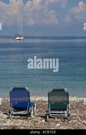 Two empty sun-loungers or sunbeds on a beach with a luxury yacht at anchor in the bay beyond. Mediterranean blue - Stock Photo