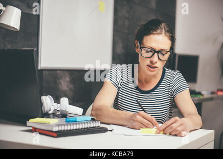 Woman wearing eyeglasses working late at the office and writing - Stock Photo