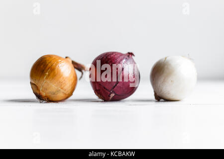 Three bulbs on a white wooden background. White onions, onions and red onions. - Stock Photo