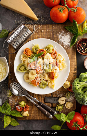 Red, white and green tortellini with vegetables and cheese - Stock Photo