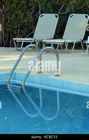 two sun loungers next to a swimming pool and reflections in the clear blue water with some handrails and steps for - Stock Photo