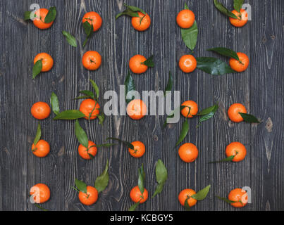 The new crop of tangerines lying in a row on dark wooden textural background - Stock Photo