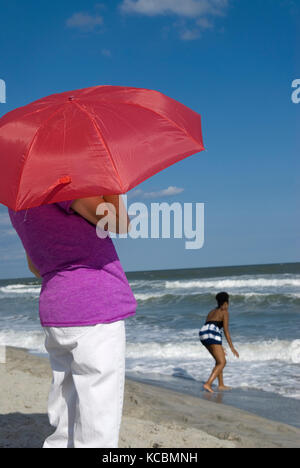 Woman holding red umbrella while viewing the ocean Myrtle Beach SC, USA. - Stock Photo