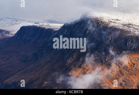 A snow and cloud covered summit of Beinn A Mhuinidh above Loch Maree in the Scottish Highlands, Scotland, UK. - Stock Photo