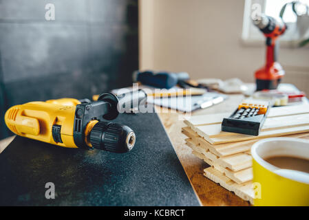 Yellow power drill and drill bits on the table with other tools - Stock Photo