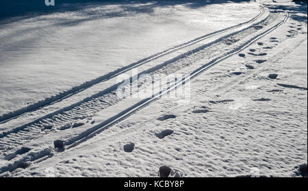 Snowmoblie tracks and footprints in illuminated snow leading into shadow. - Stock Photo